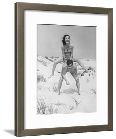 Young Couple on Beach, Woman Leap-Frogging Man, Portrait