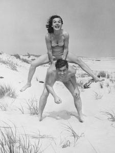 Young Couple on Beach, Woman Leap-Frogging Man, Portrait by George Marks