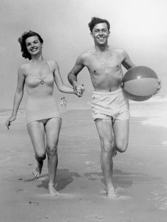 Young Couple Running on Beach With Beach Ball