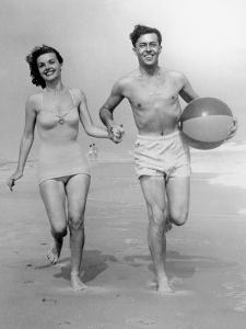 Young Couple Running on Beach With Beach Ball by George Marks