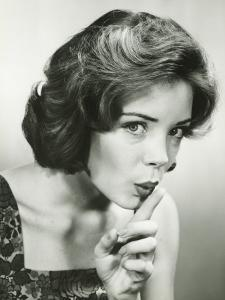 Young Woman Holding Finger on Lips, Posing in Studio, (Portrait) by George Marks