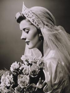 Young Woman in Wedding Dress and Bouquet in Studio, Close-Up by George Marks