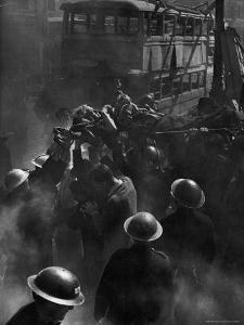British Female Casualty of German Robot Bombing Being Lifted on Stretcher by Rescue Squad by George Rodger