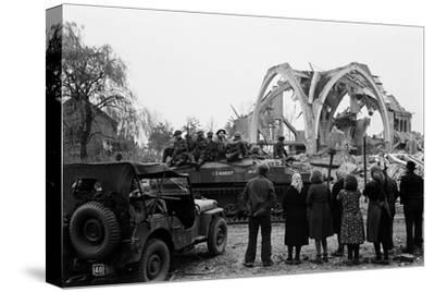 British 49th Armoured Personnel Carrier Regiment Tank Passes Civilians and a Damaged Church