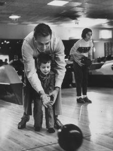 Dad Showing 3 Year Old Daughter the Basics of Bowling by George Silk