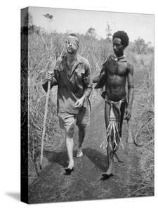 Papuan Native Helping a Wounded Australian Infantryman Along Road Away from the Buna Battlefront by George Silk