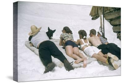 Skiers Sunbathing in Summer Fashions with Dog at Sun Valley Ski Resort, Idaho, April 22, 1947