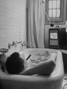 Writer Russell Finch Taking Portable Television Set to Bathroom During His Bath by George Skadding