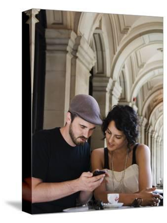 Couple at Cafe at Gpo Using Mobile Phone to Access Travel Information