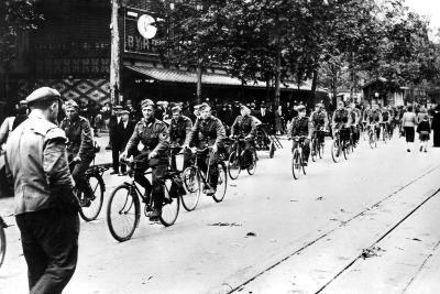 German Soldier Cycling Through the Streets of Paris, June 1940--Photographic Print