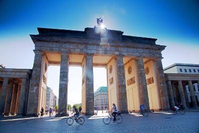 Germany, Berlin. Cyclists Passing under the Brandenburg Gate-Ken Scicluna-Photographic Print