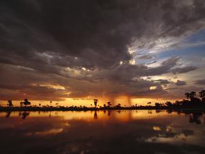 Sunset and Storm Clouds over Waterhole, Linyanti Swamp, Okavango Delta, Botswana by Gerry Ellis