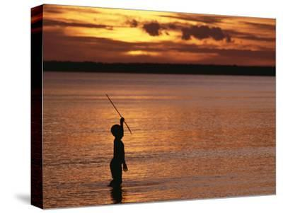 Young Boy Spear Fishing at Sunset in the Mouth of the Kikori River Delta, Papua New Guinea