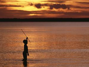 Young Boy Spear Fishing at Sunset in the Mouth of the Kikori River Delta, Papua New Guinea by Gerry Ellis