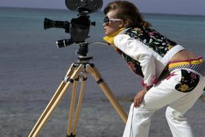 Model, in a Short White Jacket and Matching White Pants with Bright Floral Print by Gianni Penati