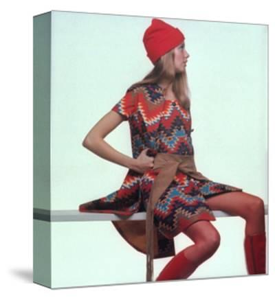 Model, Sitting on White Slat, Wears Bright Red and Blue Aztec-Print Sleeveless Coat