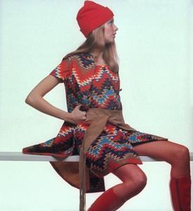 Model, Sitting on White Slat, Wears Bright Red and Blue Aztec-Print Sleeveless Coat by Gianni Penati