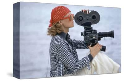 Side View of Model Holding a Movie Camera, Filming in Paradise Island, Bahamas