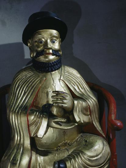 Gilt statue of Marco Polo holding a pomegranate, symbol of wealth and prosperity-Werner Forman-Photographic Print