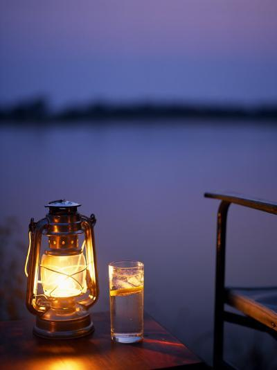 Gin and Tonic by the Light of Hurricane Lamp, Looking Out over the Zambezi River, Zambia-John Warburton-lee-Photographic Print