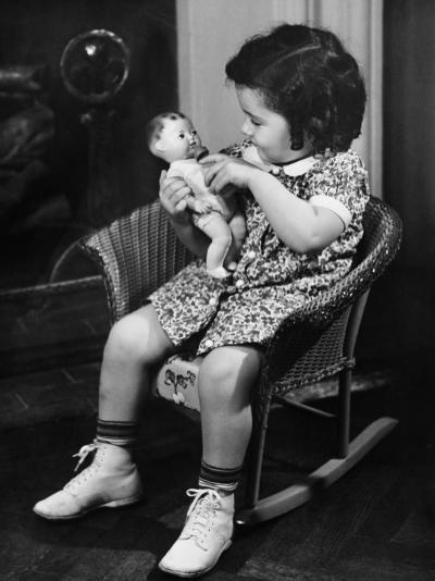 Girl (3-4) Sitting on Rocking-Chair, Playing with Doll-George Marks-Photographic Print