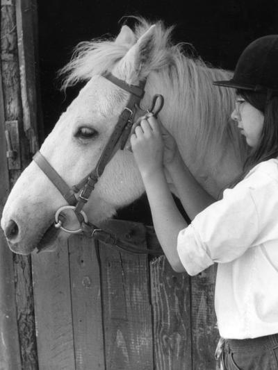 Girl Bridling Horse--Photographic Print