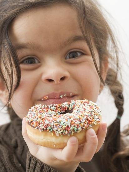 Girl Holding a Doughnut with Sprinkles, Partly Eaten--Photographic Print