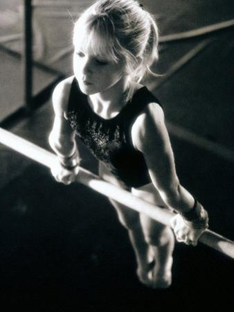 Girl Performing Gymnastics on Uneven Parallel Bars