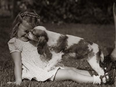 Girl Sitting Outside on Grass, Squinting While a Cocker Spaniel is Licking Her Face-H^ Armstrong Roberts-Photographic Print