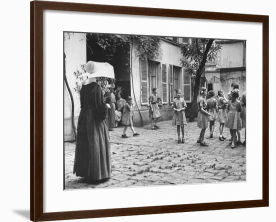 Girls Gathering in the Courtyard of the Mission, Nuns Nearby--Framed Photographic Print