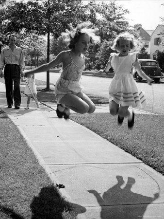 https://imgc.artprintimages.com/img/print/girls-on-the-street-in-neighborhood-using-rope-to-jump-in-tandem-while-man-with-toddler-watches_u-l-p447gi0.jpg?p=0
