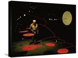 Alexander Calder Walking Past Exhibit of His Mobiles at the Guggenheim Museum by Gjon Mili