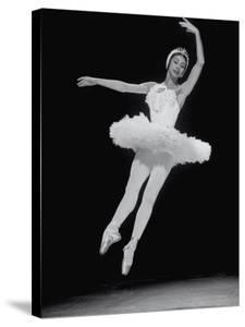 Ballerina Margot Fonteyn in White Costume Leaping into the Air While Dancing Alone on Stage by Gjon Mili