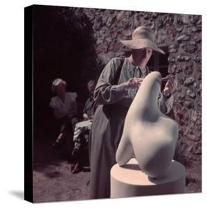French Sculptor Jean Arp, Alone, Polishing Abstract Sculpture in His Garden Near Paris by Gjon Mili