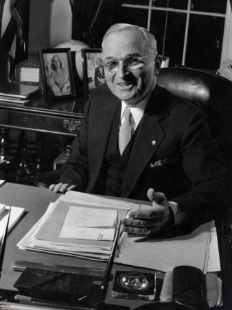 Pres. Harry S. Truman Seated at His Desk in the White House, Family Photographs on Table Behind Him