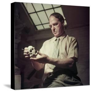 Sculptor Henry Moore Holding a Small Sculpture in His Studio in Much Hadham, England by Gjon Mili