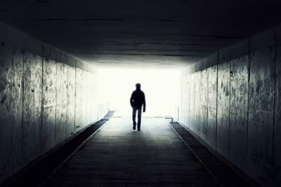 Silhouette Of Man Walking In Tunnel. Light At End Of Tunnel by Gladkov