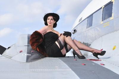 Glamorous Woman in 1940's Style Attire Sitting on a Vintage Aircraft--Photographic Print