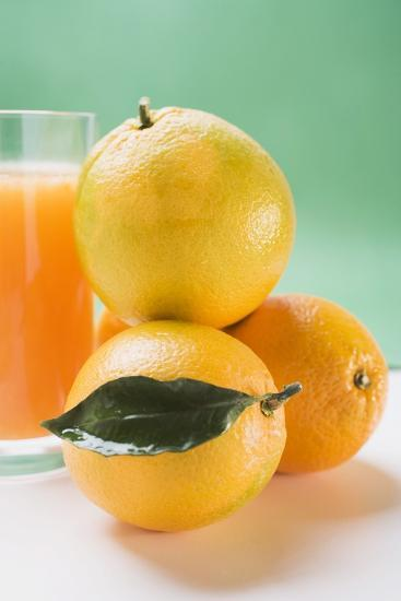 Glass of Orange Juice Beside Several Oranges-Foodcollection-Photographic Print