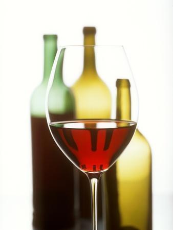 https://imgc.artprintimages.com/img/print/glass-of-red-wine-in-front-of-three-wine-bottles_u-l-q10soui0.jpg?p=0
