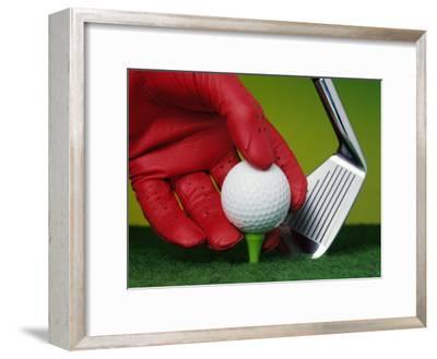 Gloved Hand Placing Golf Ball on Tee