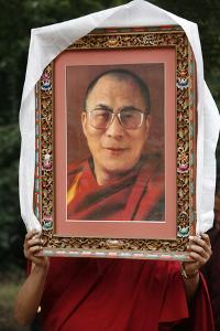 Buddhist holding a picture of the Dalai Lama, Ile de France, France by Godong