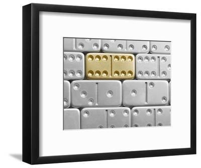 Gold domino amid silver dominoes