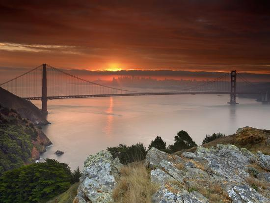 Golden Gate Bridge At Sunset Under Foggy And Cloudy Skies