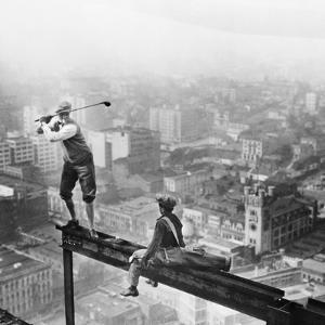 Golfer Teeing off on Girder High above City