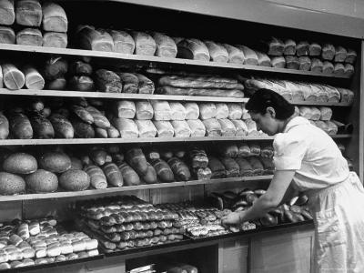 Good of Worker in Bakery Standing in Front of Shelves of Various Kinds of Breads and Rolls-Alfred Eisenstaedt-Photographic Print