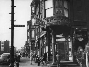 Corner Drugstore and Pedestrian Traffic on W. Oak St. in the Italian Section of Chicago by Gordon Coster