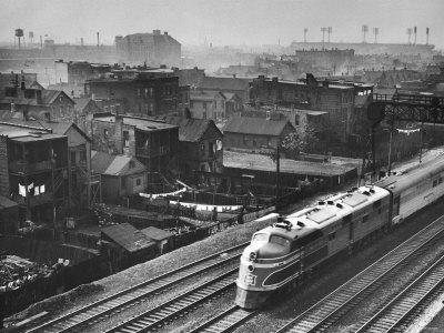 Train Moving Past Trackside Tenement Slums of Chicago