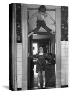 "Denise Bruene Climbing Kitchen Door in Bare Feet, Her Hobby, Jan Bruene Says ""Don't Fall on Me"" by Gordon Parks"