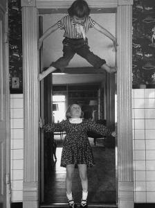"""Denise Bruene Climbing Kitchen Door in Bare Feet, Her Hobby, Jan Bruene Says """"Don't Fall on Me"""" by Gordon Parks"""